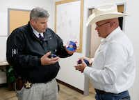 Wise County sheriff investigator Luke Campbell hands over DVD copies of evidence to special ranger John Bradshaw of the Texas and Southwestern Cattle Raisers Association.(Vernon Bryant/Staff Photographer)