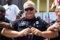 """Dallas Police motorcycle officer Earl """"Jamie"""" Givens and others hold their hands in the symbol of a heart during a Weekend of Honor event at Southwest Center Mall on Saturday, July 8, 2017, in Dallas. Participants attempted to break the world record for most people linked at the arms holding a heart shape.(Ryan Michalesko/Staff Photographer)"""