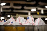 Priority Mail parcels fill a large container at the US Postal Service's North Texas Processing & Distribution Center in Coppell, Texas, Thursday, December 14, 2017.(Tom Fox/Staff Photographer)