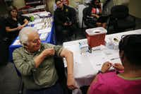 Gavino Saldivar, of DeSoto, Texas, lifts his sleeve up before receiving an influenza vaccine from Barbara Davis (right), a registered nurse, at a mobile immunization clinic hosted by Dallas County Health and Human Services at the DeSoto Senior Center in DeSoto Tuesday February 20, 2018. According to Renae Crutchfield, public information officer for Dallas County Health and Human Services, the county was focusing on reaching the elderly since that population is the most vulnerable to the influenza. (Andy Jacobsohn/Staff Photographer)