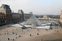 People walk around the pyramid of the Louvre, designed by Chinese-American architect I.M. Pei, outside the Louvre museum in Paris.(2017 File Photo/Agence France-Presse)