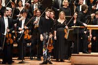 Violinist Blake Pouliot (center) smiled as he was introduced on Thursday night. Clad in colorful rock star pants, he would go on to dispatch virtuoso licks with panache.(Ben Torres/Special Contributor)