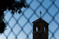 The steeple is seen through a fence outside of St. Cecilia Catholic Church during an evening mass on Wednesday, May 15, 2019 in Dallas. Dallas police raided the Catholic Diocese of Dallas earlier today after an investigation into child sexual abuse allegations against a former priest uncovered claims against others. (Ashley Landis/The Dallas Morning News)(Ashley Landis/Staff Photographer)