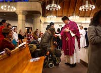 "Michael ""Migue""' Moon, 51, of Dallas received communion from the Rev. Joshua Whitfield at St. Rita Catholic Community last year.(Tom Fox/Staff Photographer)"