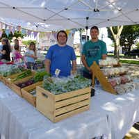 Tree Folk Farm co-owner Matt Gorham from Denton (right) gets a hand from Mark Garza at Lakewood Village Farmers Market, Tree Folk's first venture with Good Local Markets.(Kim Pierce)