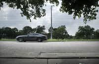 A car passes by the spot on Valley Glen Dr. (foreground) where Muhlaysia Booker's body was found Saturday near Tenison Golf Course in Dallas.(Tom Fox/Staff Photographer)