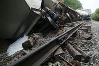 A white substance spilled from one of the cars lying tilted off the tracks Wednesday morning after a train derailment Monday night on the railroad line leading through the Tenison Park Golf Course near the 3600 block of Samuell Boulevard on the east side of Dallas.(Michael Hamtil/Staff Photographer)