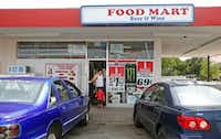 A man and his son leave the Mart Smart convenience store on Oates Drive near the Ferguson Road intersection after buying a gallon of milk and some candy. The area has several small convenience stores, a 7-Eleven and many restaurants, but the nearest grocery is several miles away.(Guy Reynolds/Staff photographer)