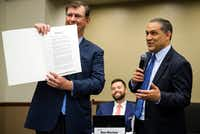 Dallas Mayor Mike Rawlings displays his Recognition of Service proclamation presented to him by DISD Board President Edwin Flores during a DISD board meeting as trustee Ben Mackey looks on Thursday.(Smiley N. Pool/Staff Photographer)