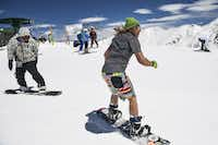 A snowboarder wearing shorts and a T-shirt enjoyed spring conditions at Arapahoe Basin Ski Area on Saturday in Dillon, Colo. Even as weekend temperatures pushed into the 50s, late-season snows have prompted Arapahoe Basin to announce plans to extend its season until at least June 16.(Michael Ciaglo/Getty Images)