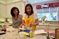 Priya Krishna, right, with her mother Ritu Krishna, work together to prepares dishes of roti and paratha at Priya's family home in Dallas.(Ben Torres/Special Contributor)