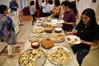 Isha Elhence, right, and Hirsh Elhence, top-right, load their plates with food during a family dinner at Priya Krishna's family home in Dallas.(Ben Torres/Special Contributor)