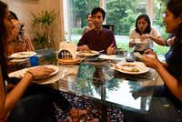 Hirsh Elhence, 24, center, speaks to his sister Meha Elhence, far-left, and cousin Isha Elhence, far-right, as they eat with Priya Krishna, right of Hirsh, during a family dinner at Priya's family's home in Dallas.(Ben Torres/Special Contributor)