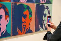 "A visitor records one of a series of self portraits at the exhibition ""Andy Warhol — From A to B and Back Again"" at the San Francisco Museum of Modern Art.(Eric Risberg/The Associated Press)"