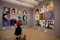 A woman views commissioned portraits created by Andy Warhol from 1968 to 1987 at the San Francisco exhibition. (Eric Risberg/The Associated Press)