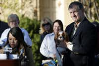 Dallas Mayor Mike Rawlings holds Bentley as Dallas nurse Nina Pham speaks to the media after Pham and Bentley were reunited following the canine finishing a 21-day monitoring period for the Ebola virus at Hensley Field in Grand Prairie on Nov. 1, 2014. Pham was cured of Ebola at the National Institute of Health in Maryland.(File Photo/Staff)