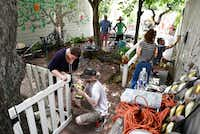 Carrie Perkins (left) and Simon Perkins work together to complete a swinging door on a fence as members of the Oak Cliff Gardeners Facebook forum renovate the backyard of the Legacy Founders Cottage.(Ben Torres/Special Contributor)