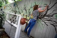 Julie Shipp, who teaches art at Collin College, volunteered to paint a tree mural on a fence at the home for patients with advanced AIDS. (Ben Torres/Special Contributor)