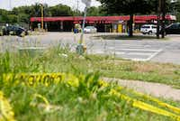Caution tape on the ground across the street from Jim's Car Wash in Dallas on Monday. Four gunshot victims were found at the car wash on Sunday evening. One was killed and four people were injured in the shooting.(Vernon Bryant/Staff Photographer)