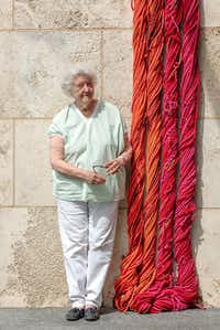 """Artist Sheila Hicks poses with a part of her """"Sheila Hicks: Seize, Weave Space"""" 2019 installation, on view through Aug. 18 at the Nasher Sculpture Center in Dallas.(Kevin Todara/Nasher Sculpture Center)"""