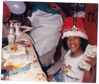 Playwright Jonathan Norton holds up money while opening presents during a childhood birthday party.