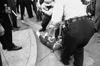 """From the Associated Press caption that accompanies this archival photo: """"Police in Jackson, Miss., club Willie Ludden Jr. of Atlanta after he resisted arrest during massive demonstration, May 31, 1963.  Ludden carried a sign and American flag in the march.""""(Jim Bourdier/Associated Press)"""