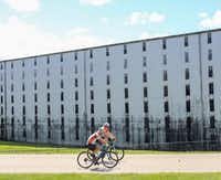 Cyclists ride past a rickhouse -- a building where bourbon barrels age — at Heaven Hill Distillery in Bardstown, Ky.(Bardstown Tourism & Convention Commission/Courtesy)