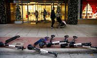 BIRD electric rental scooters lie on the ground outside the Neiman Marcus store in downtown Dallas, Friday, December 14, 2018. (Tom Fox/Staff Photographer)