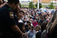 "Eric Molina looks up at his father, Grand Prairie police Officer Edgar Molina, as his sister, Rebecca Molina, 6, looks on during Sunday's vigil for Officer Albert ""A.J."" Castaneda at the Grand Prairie Public Safety Building.(Shaban Athuman/Staff Photographer)"