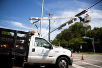 <p>A city of Dallas employee works on traffic lights near the Dallas Arboretum on Monday. Strong storms produced widespread damage throughout Dallas-Fort Worth, causing more than 200,000 people to lose power.</p>(Shaban Athuman/Staff Photographer)