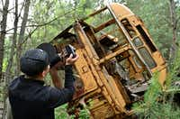 A visitor photographs the wreckage of a bus in the ghost city of Pripyat. The city was evacuated on April 27, 1986, a day after the Chernobyl nuclear disaster.(Genya Savilov/Agence France-Presse/Getty Images)