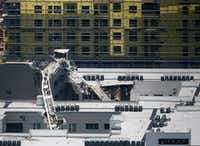 A collapsed tower crane operated by Bigge Crane and Rigging lies where it fell on top of the Elan City Lights apartment building Wednesday in Dallas. In the background is The Gabriella, the building under construction  where the crane stood before it fell during a severe storm Sunday.(Michael Hamtil/Staff photographer)