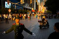 "<p><span style=""font-size: 1em; background-color: transparent;"">To keep the crowds out of traffic, soldiers were stationed every few meters on East Nanjing Road. Eventually, this area turned into a pedestrian-only mall lined with shops. At the end of the mall, I kept walking under a highway underpass and the crowds thinned out as I approached the trees of People's Square.</span></p>(Smiley N. Pool/Staff Photographer)"