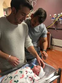 Dallas residents Alex Reyher (left) and Ryan Layman (right) welcome their newborn, Rory. The couple chose surrogacy in their family planning and ended up influencing a change in how Layman's employer, PwC, provides benefits like surrogacy reimbursement.(Courtesy of Ryan Layman)
