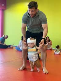 Ryan Layman helps his son, Rory, walk upright. Layman and his husband chose surrogacy in their family planning and ended up influencing a change in how Layman's employer, PwC, provides benefits like surrogacy reimbursement. Newborn Rory wears a helmet to reshape a flat spot on his head.(Courtesy of Ryan Layman)