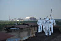 Visitors take a rooftop selfie with the Chernobyl nuclear power plant in the background. Most visitors opt for regular attire.(Chernobyl Tour/chernobyl-tour.com)