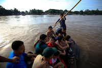 A group of more than a dozen Honduran migrants ride a raft across the Suchiate river after between Tecun Uman, Guatemala, top, and Ciudad Hidalgo, Mexico, Friday, June 14, 2019. Raftsmen and riverfront business operators said the flow of migrants through the crossing has slowed since the announcement a few days ago that Mexico's new National Guard would be deploying to the border.(Rebecca Blackwell/AP)