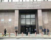 Law enforcement officers secure the scene after a man fired shots at the Earle Cabell federal building and courthouse in downtown Dallas on Monday morning, June 17, 2019.  A revolving door at the main entrance along Commerce Street was shattered.(Tom Fox/Staff photographer)