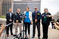 Erin Nealy Cox, center, U.S. Attorney for the Northern District of Texas, addresses the media ,along with FBI Special Agent in Charge Matt DeSarno, second right, after a man was shot and killed after shooting at the federal courthouse in Dallas.(Shaban Athuman/Staff Photographer)