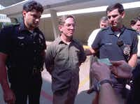 """Dallas police read George Douglas Lott, center, his rights after he turned himself in to the Dallas police in 1992.  Lott, 45, said he attacked courthouse workers to draw attention to his son and his four-year-old <nobr style=""""font-size: inherit""""><a id=""""PXLINK_0_0_0"""" class=""""pxInta"""" href=""""#"""">divorce</a></nobr> case.&nbsp;(Associated Press)"""