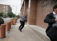 A security guard and a civilian run for cover as bullets ricochet off the building as a shooter (far background left) fires toward them on Monday, June 17, 2019, at the Earle Cabell Federal Building in Dallas.(Tom Fox/Staff Photographer)