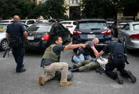Members of the Department of Homeland Security and the U.S. Marshals Service tend to the downed shooter after shots were fired Monday morning at the Earle Cabell Federal Building in Dallas.(Tom Fox/Staff Photographer)