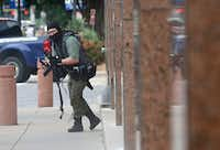 <i>Dallas Morning News</i> photojournalist Tom Fox captured this image of Brian Isaack Clyde advancing toward the south entrance of the Earle Cabell Federal Building Monday morning, shortly after Clyde had opened fire on the building from across the street.(Staff Photographer/Tom Fox)