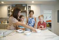Kristen Massad preparing granola bars with her daughters Adele Massad (6) and Sophie Massad (8) and a family friend Sam Booke (6) at her home in Dallas.(Lawrence Jenkins/Special Contributor)