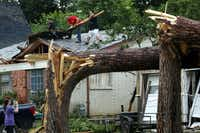 Volunteers help residents along Andrews St. clear roof debris in north Arlington after large trees were toppled Sunday.(Tom Fox/Staff Photographer)