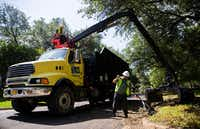 Juan Salamanca (left) and Albert Tims of Looks Good Services, which contracts with the city of Dallas, collect debris left behind from recent storms on Friday, June 21, 2019, on Cliffbrook Drive in Far North Dallas.(Ashley Landis/Staff Photographer)