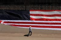 "<p>Mexican U.S. resident Roberto&nbsp;<span style=""font-size: 1em; background-color: transparent;"">Márquez&nbsp;</span><span style=""font-size: 1em; background-color: transparent;"">places a U.S. flag on the border fence next to Rio Grande in El Paso in protest of the immigration policies of President Donald Trump on June 6, 2019.&nbsp;</span></p>(HERIKA MARTINEZ/AFP/Getty Images)"