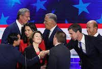 <p>Julian Castro and Beto O'Rourke shake hands after the first Democratic presidential debate on June 26, 2019 in Miami, crossing arms between moderator Chuck Todd of NBC and Sen. Amy Klobuchar.</p>(Joe Raedle/Getty Images)