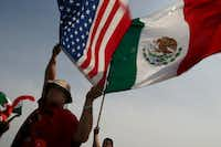 Eduardo Marquez (left) and Jaime Rosas, 14, wave the American and Mexican flag during a protest at Kiest Park in Dallas on March 28, 2006.(LAWRENCE JENKINS/<i>The Dallas Morning News</i>)