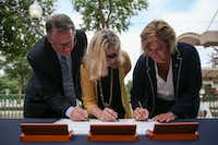 From left: DART Executive Director Gary Thomas, DART Board of Directors chairwoman Sue Bauman and acting Federal Transit Administration Administrator K. Jane Williams sign a full funding grant agreement during an announcement of expansion to the downtown Plano DART station on Thursday.(Ryan Michalesko/Staff Photographer)